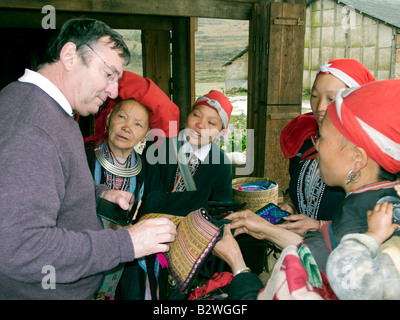 Red Dzao hilltribe women clamour round tourists and tourist buses to sell handicrafts Ta Phin village near Sapa - Stock Photo