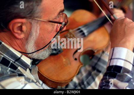 A local man plays violin for passers-by in the craft market of Tel Aviv, Nahalat Binyamin. - Stock Photo