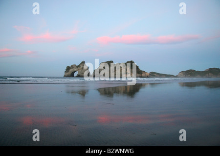 Sunset over Wharariki Beach on the West Coast from Golden Bay, South Island, New Zealand - Stock Photo