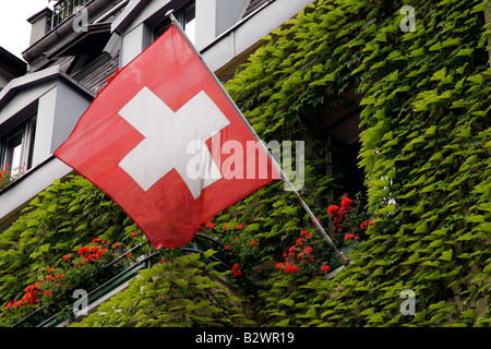 Swiss flag on the side of a building covered with a creeper and geranium window boxes in Lucerne, Central Switzerland - Stock Photo
