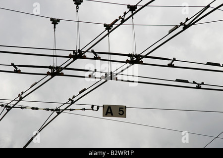 Overhead tram wires cross at a busy intersection in Lucerne, Central Switzerland - Stock Photo