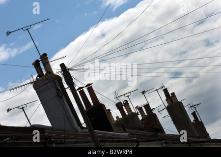 TV aerials and chimneypots on the skyline above a row of terraced houses - Stock Photo
