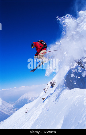 Skier jumping on snowy hill - Stock Photo