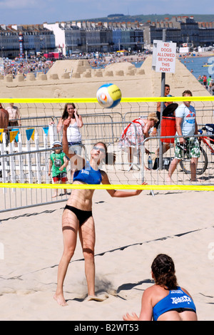 College girls playing summer beach Volleyball - Stock Photo