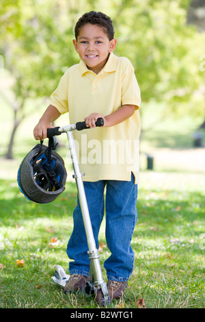 Young boy outdoors on scooter smiling - Stock Photo