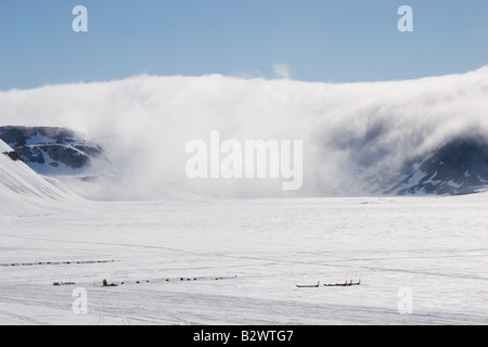 Cloud rolls over the mountains onto the frozen sea ice of Scoresbysund fjord, Ittoqqortoormiit, East Greenland - Stock Photo