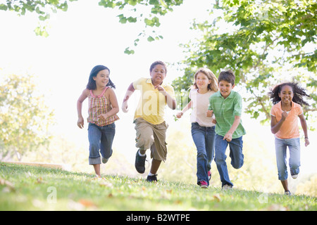 Five young friends running outdoors smiling - Stock Photo