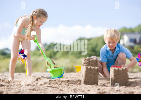 Brother and sister at beach making sand castles - Stock Photo
