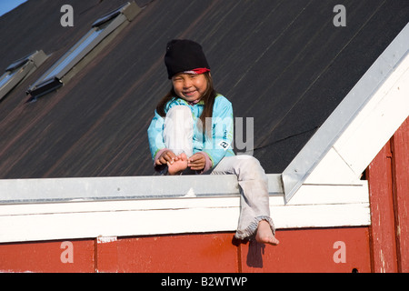 A young Inuit girl plays on the post office roof in the village of Ittoqqortoormiit, Scoresbysund, East Greenland - Stock Photo
