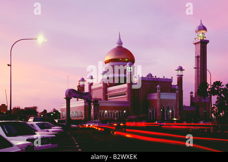 Asia Brunei Bandar Seri Begawan Famous Omar Ali Saifuddin Mosque at sunset with streaks of rear lights in foreground - Stock Photo