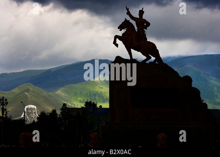 The statue of the hero Sukhbaatar is overlooked by a huge image of Genghis Khan in chalk on the hillside overlooking - Stock Photo