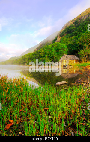 A small boathouse on a beautifully calm and misty morning at Llyn Dinas in Snowdonia national park North Wales - Stock Photo