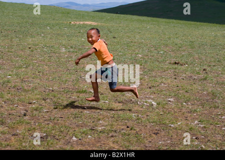 Mongolian boy running and laughing in the countryside - Stock Photo