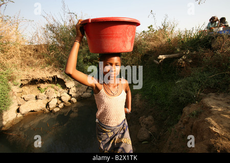 African girl collecting water from a dirty river, Northern Nigeria, West Africa - Stock Photo