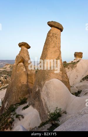 Fairy chimneys known as The Three Beauties illuminated at night, near Goreme, Cappadocia, Central Anatolia, Turkey - Stock Photo