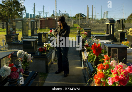 A woman walks through graves backed by powerlines. - Stock Photo