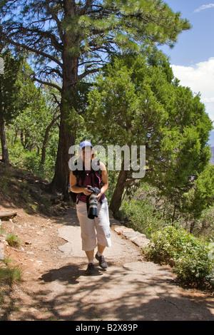 Woman photographer walking up a path - Stock Photo