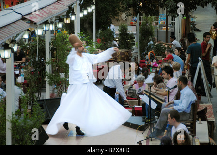 A Dervish dancer performing in a restaurant - Stock Photo