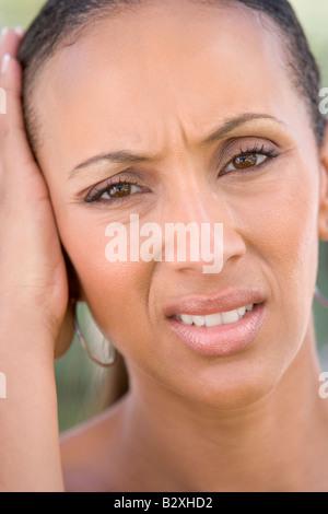 Head shot of woman scowling - Stock Photo