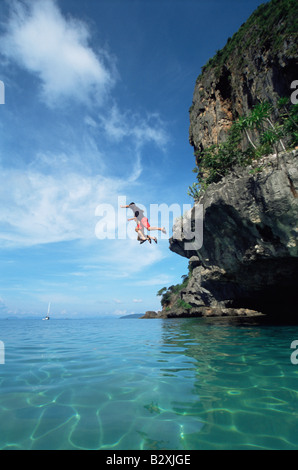 Couple outdoors jumping off cliff into ocean - Stock Photo
