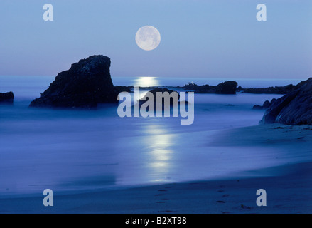 Moon setting over rocky shore along Pacific Coast in Laguna Beach, California - Stock Photo