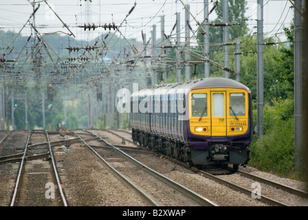 class 319 train in first capital connect livery travelling beneath catenary in the uk - Stock Photo
