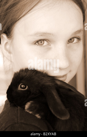 Portrait of a young girl holding a black baby rabbit in sepia - Stock Photo