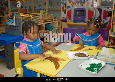 Two 4 year old African American girls finger painting in preschool class - Stock Photo