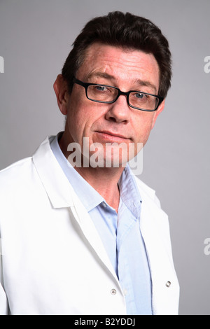 Male 40 something doctor smiling wearing a white coat -glasses - Stock Photo