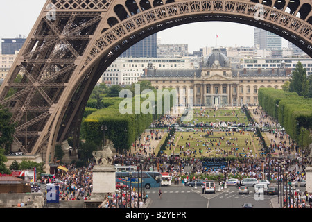 Groups of people in the shadow of the Eiffel Tower and Parc du Champ de Mars in the background Paris France - Stock Photo