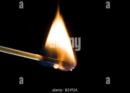 Macro shot of a burning match against a black background - Stock Photo
