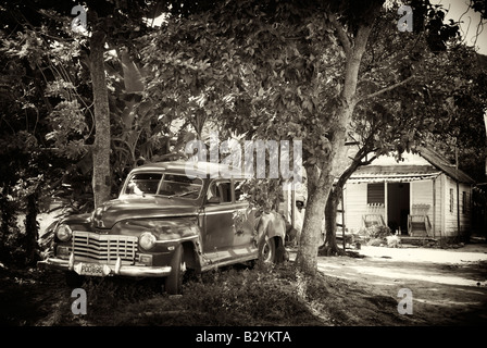 OLD CLASSIC 1950 s VINTAGE AMERICAN CAR PARKED OUTSIDE WOODEN HOUSE IN VIÑALES AREA OF CUBA - Stock Photo