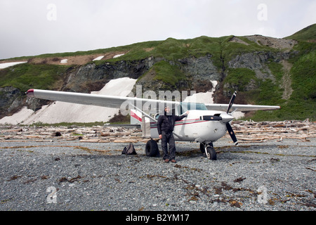 K-Bay Air air plane (Cessna 206) and pilot standing on a beach filled with driftwood in the Katmai National Park - Stock Photo