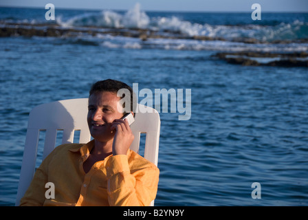 a businessman sitting and talking on the phone near the sea - Stock Photo