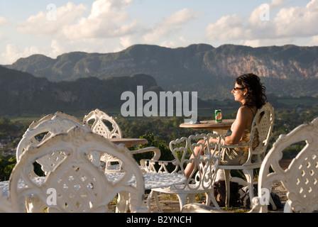Model Released European tourist enjoying the view across a valley to steep mogote limestone hills of Viñales Cuba - Stock Photo
