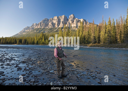Man Fishing in Mountain River, Banff National Park, Alberta, Canada - Stock Photo