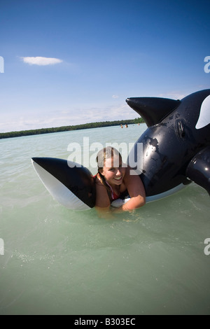 Girl in Water with Inflatable Whale - Stock Photo