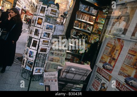 Woman using cellphone by postcard rack of magazine stall. Paris, France. - Stock Photo