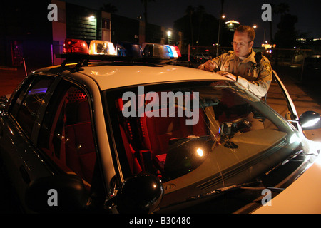 Las Vegas police officer writing report on roof of car at night - Stock Photo