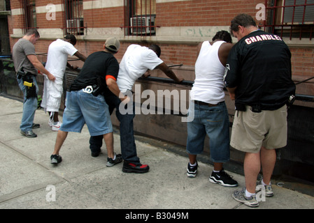Plainclothes anti-crime police detectives searching suspects in Harlem New York City - Stock Photo
