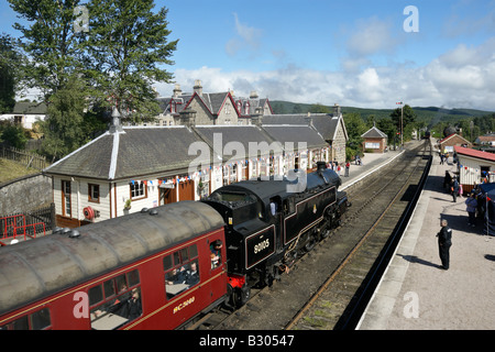 Steam train arriving at Boat of Garten Station from Aviemore - Stock Photo