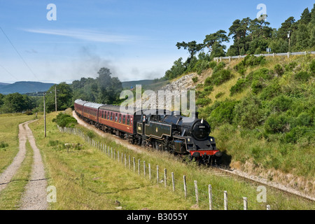 Steam train approaching Broomhill on the Strathspey Steam Railway - Stock Photo