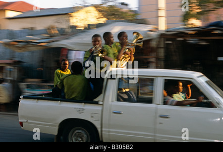 Men traveling in back of pick-up truck playing brass instruments, street scene South Africa, Africa - Stock Photo