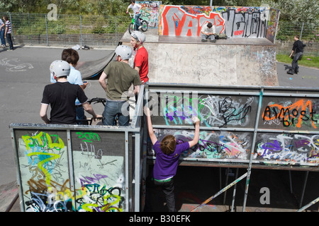 Boy drawing graffiti on bike on ramp in skateboard park. Merseyside England UK - Stock Photo