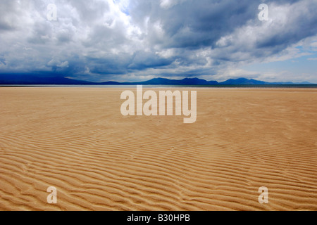 A wide expanse of flat sandy beach at Newborough Warren on Anglesey North Wales with the Lleyn Peninsula on the - Stock Photo