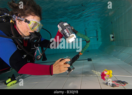 Woman scuba diver practices underwater photography in swimming pool - Stock Photo