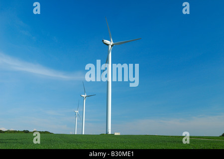 Three windturbines on blue sky and green field -  France - Stock Photo