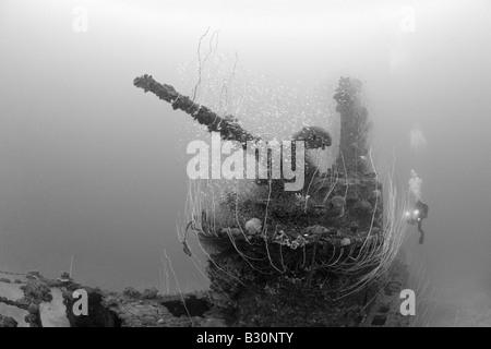 Diver and 5 inch Deck Gun of USS Apogon Submarine Marshall Islands Bikini Atoll Micronesia Pacific Ocean - Stock Photo