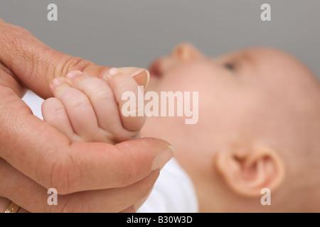 Women's hand and Baybfinger - Stock Photo