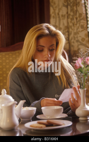 woman reading bill for coffee and biscuits - Stock Photo